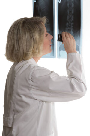 Doctor of radiology examining x-ray with magnifying glass, isolated on white 免版税图像