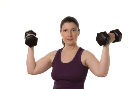 fitnesscenter: Middleaged woman in muscleshirt with two dumbbells, isolated