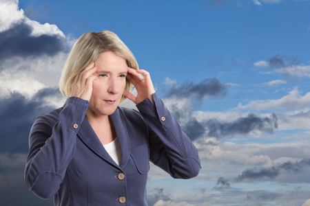 Middle aged woman being weather sensitive and suffering from a headache, copy space photo