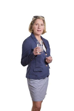 falda corta: Mujer rubia de mediana edad en chaqueta y falda corta con un vaso de agua con cubos de hielo, aislados en blanco, copia espacio Foto de archivo