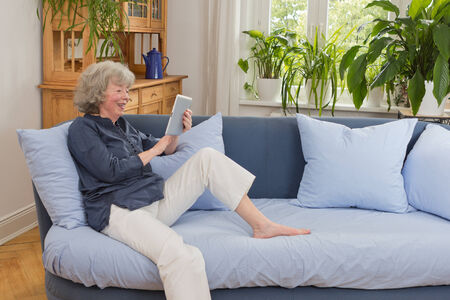 Laughing pensioner sitting with tabletpc on her sofa, copy space photo