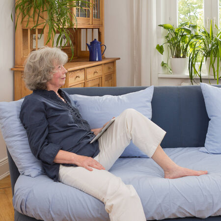 Senior woman sitting thoughtfully with a tablet computer on the sofa in her living room, square photo