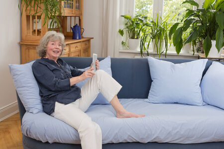 Smiling elderly woman sitting casually with a tablet pc on her couch, copy space photo