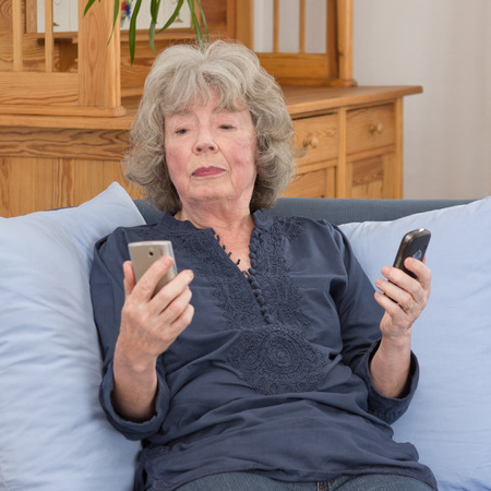 Confused elderly lady with two mobile phones on her sofa, square photo