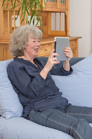 Relaxed and happy aged woman sitting with tablet pc on her sofa 免版税图像