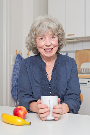 zest for life: Happy pensioner with mug, banana and apple at kitchen table Stock Photo