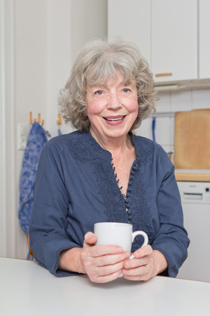 vivacious: Portrait of a vivacious senior woman at her kitchen table with a mug