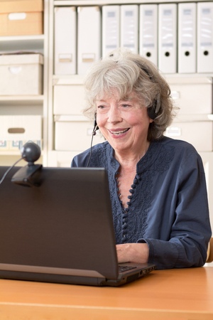 Senior woman with headphone smiling at the webcam of her laptop, copy space