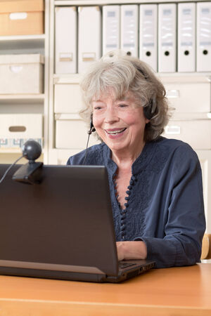 grey haired: Grey haired woman sitting in front of her computer having a video chat, copyspace