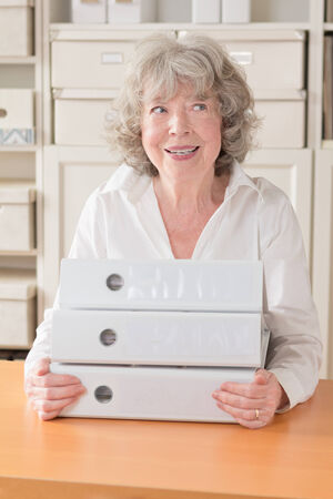 grey haired: Smiling grey haired woman with files, copy space Stock Photo