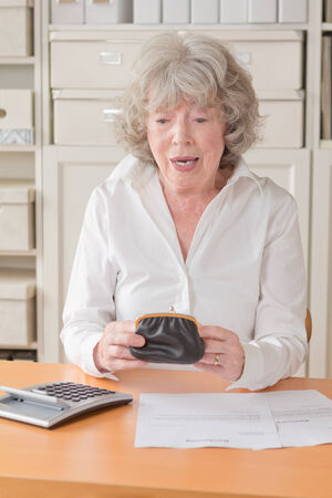 Senior woman with bills and calculator looking horrified into her purse photo