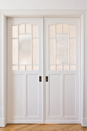 frontal view: White sliding doors art nouveau style in a room with oak parquet flooring, frontal view Stock Photo
