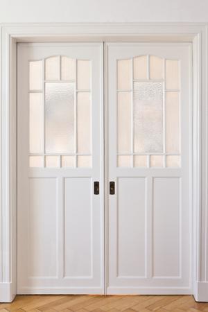 Witte schuifdeuren art nouveau-stijl in een kamer met eiken parketvloer, vooraanzicht