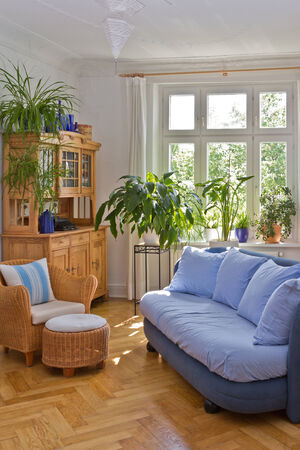 cane sofa: Bright living room in old building with stucco, sofa, armchair, stool and antique cupboard in blue and warm colors Stock Photo