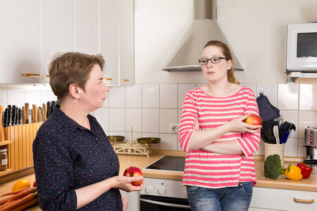Young and old woman in kitchen with two apples in their hands and bad mood