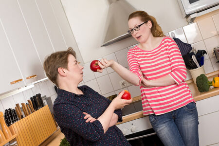 reluctance: Mother and daughter in kitchen with apples in their hands having a discussion