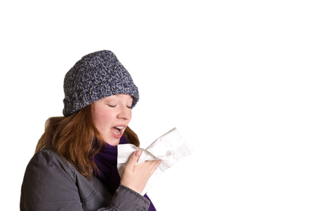 sneezing: Sneezing woman with handkerchief in warm clothes, isolated, copy space