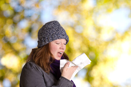 Sneezing young woman with woolen hat, scarf and handkerchief outdoors in front of tree, copy space photo