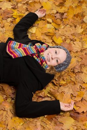 warm clothes: Giovane donna avvolta in vestiti caldi sdraiata su foglie di acero e ridendo pieno di gioia