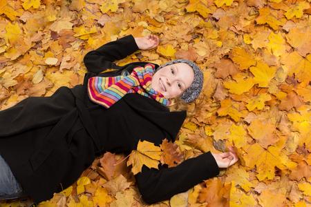 joie: Joyful junge Frau mit Lebensfreude auf Gold farbigen Ahorn Bl�tter liegen, Kopie, Raum Lizenzfreie Bilder