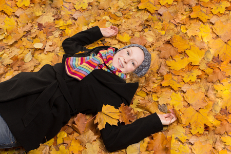 zest for life: Joyful young woman with zest for life lying on gold colored maple leaves, copy space