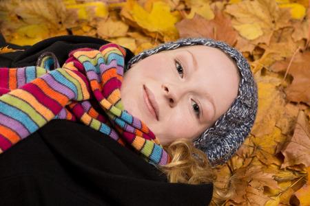 radiating: Avvolto bella donna sdraiata su foglie gialle in autunno, sorridente, irradiando gioia
