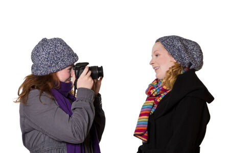 winter photos: Two young women in winter clothes taking photos of each other, isolated, copy space Stock Photo