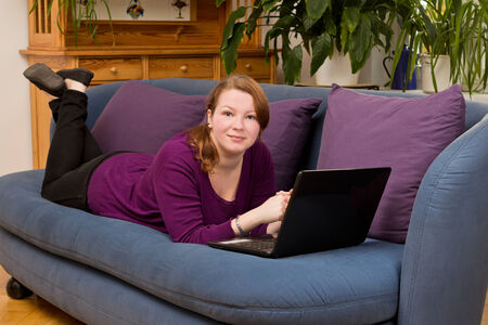 Cheerful young woman relaxing on sofa with her laptop, copyspace photo