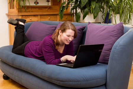 Pretty young woman lying on couch with a laptop smiling, copyspace photo