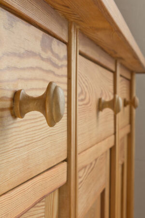 Three drawers of a wooden cabinet or a chest with knobs, pigeon-hole thinking  Stock Photo