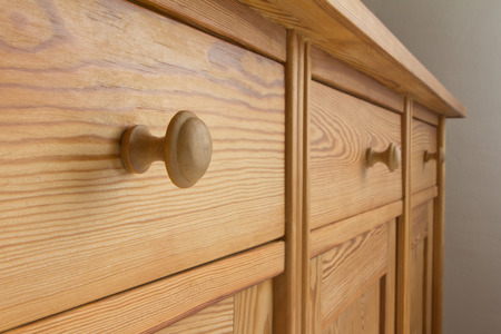 categorization: Three drawers of a chest of drawers with knobs, soft wood, orderiness