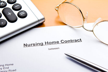 nursing care are for seniors: A contract for a nursing or retirement home with calculator, reading glasses and ballpoint pen