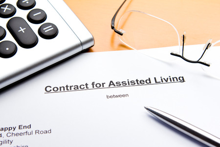assisted living: Contract for Assisted Living with calculator, glasses and ballpoint pen