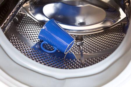 forgetfulness: Blue mug and spoon in washing machine drum, symptom of dementia