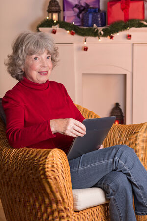 Happy elderly lady with e-reader in front of fireplace with festive decoration at Christmas photo