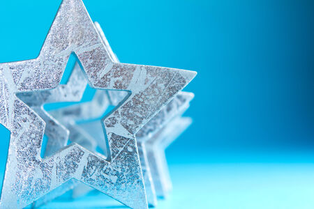Close-up silver stars on turquoise-blue background, copyspace