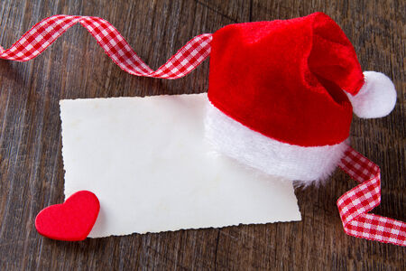 Father Christmas cap with yellowed card, red heart and checkered ribbon on dark wood, copy space photo
