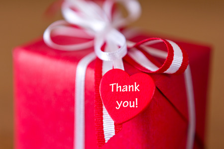 Red present with white bow and heart on brown background, text, thank you! 免版税图像