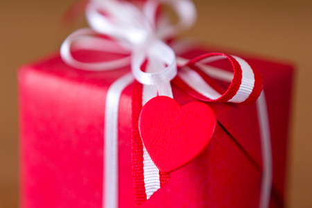 Red present with white bow and heart on dark wood, copy space photo