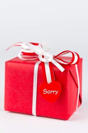 Red gift box with white bow and a heart, text sorry,  isolated, copy space