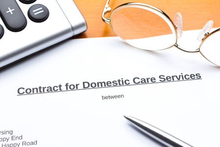 Contract for a home care service with calculator, reading glasses and biro 免版税图像