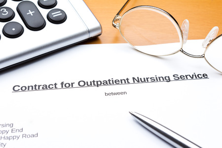 Contract about a nursing service on an outpatient basis with calculator, reading glasses and ballpoint pen