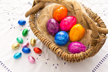 basket embroidery: Colorful Easter eggs in and in front of a basket on a white table cloth with embroidery