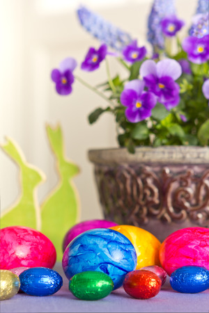 Colorful Easter Eggs with two bunnies and a pot of pansies photo