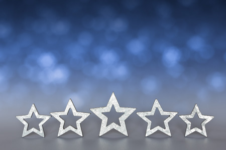 five stars: Five silver stars on blurred blue and gray background copyspace