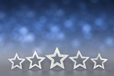 Vijf zilveren sterren op wazig blauwe en grijze achtergrond copyspace