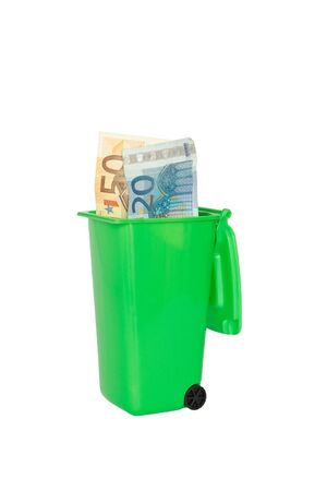 wasting away: Euro banknotes in a green rubbish or garbage bin isolated copyspace Stock Photo