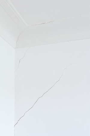 foundation cracks: White wall and ceiling with stucco of a room in an old house with a long crack or rip, structural damage
