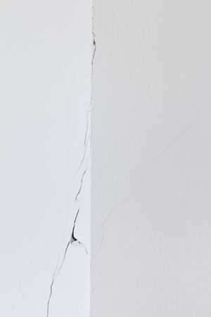 foundation cracks: Corner of a white wall in a room in an old house with a long crack or rip, structural damage