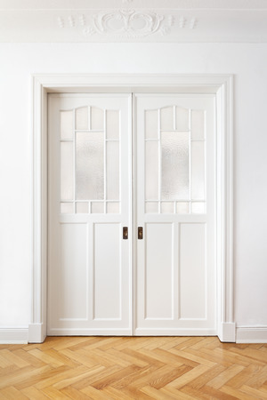 White old double sliding door with textured glass in an historic building with stucco, copy space Standard-Bild